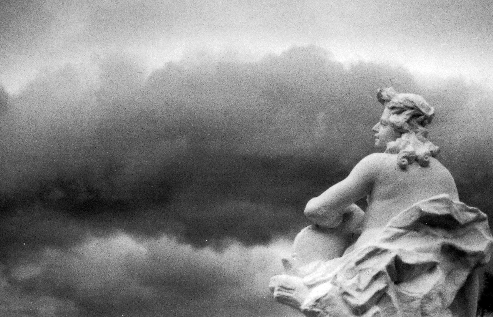 A statue of a person with flowing hair sits, gracefully looking over from right to left. The background depicts a texture of greyish clouds.
