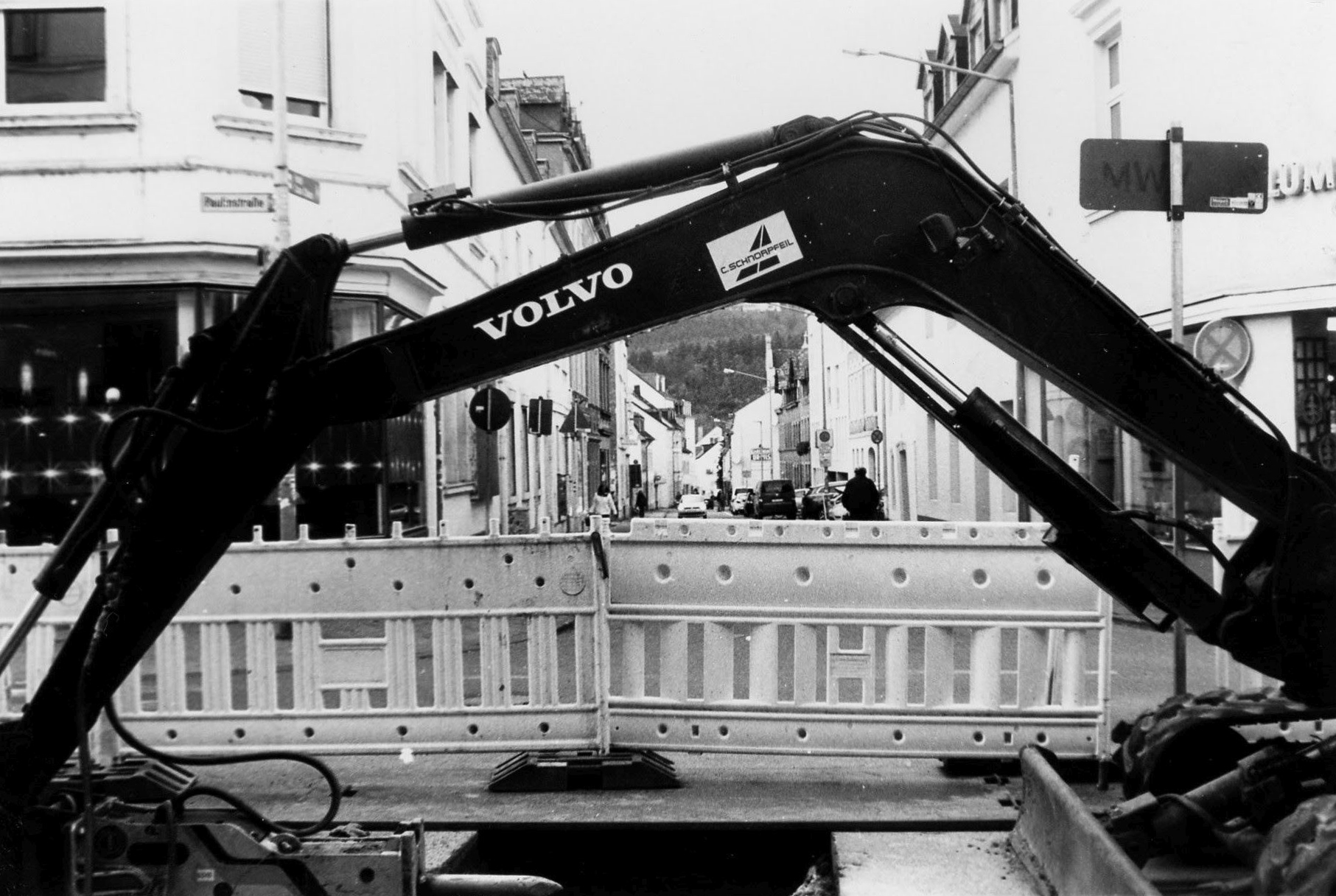 """A halted construction site, the arm of a power shovel (that says """"Volvo"""") in the front, a whole at the bottom, in the background a city's crossroad, a street goes into the background."""