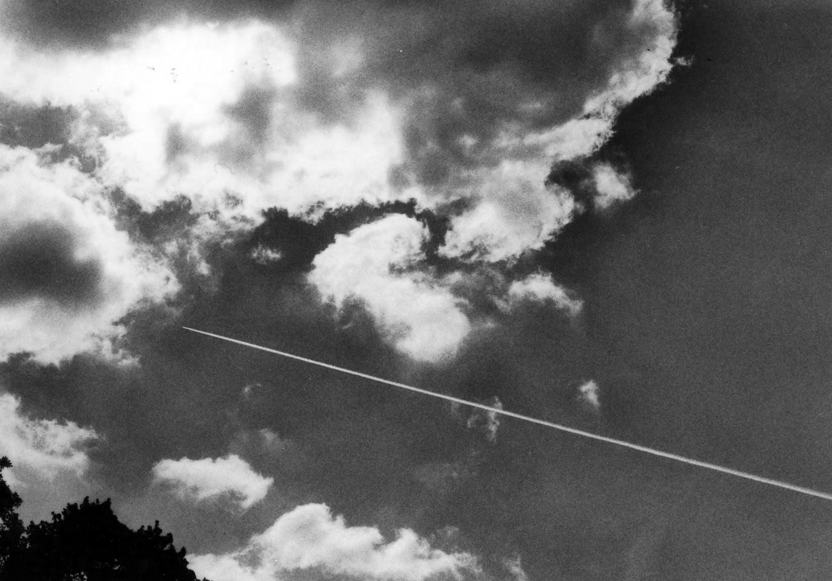 Sky. Condensation trail piercing into clouds.