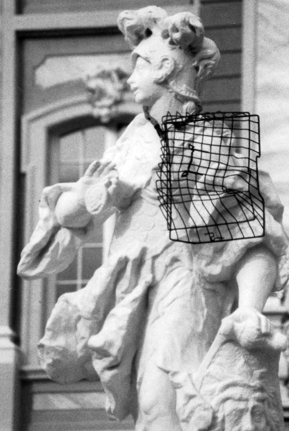 White statue with a black grid basket hanging on it.