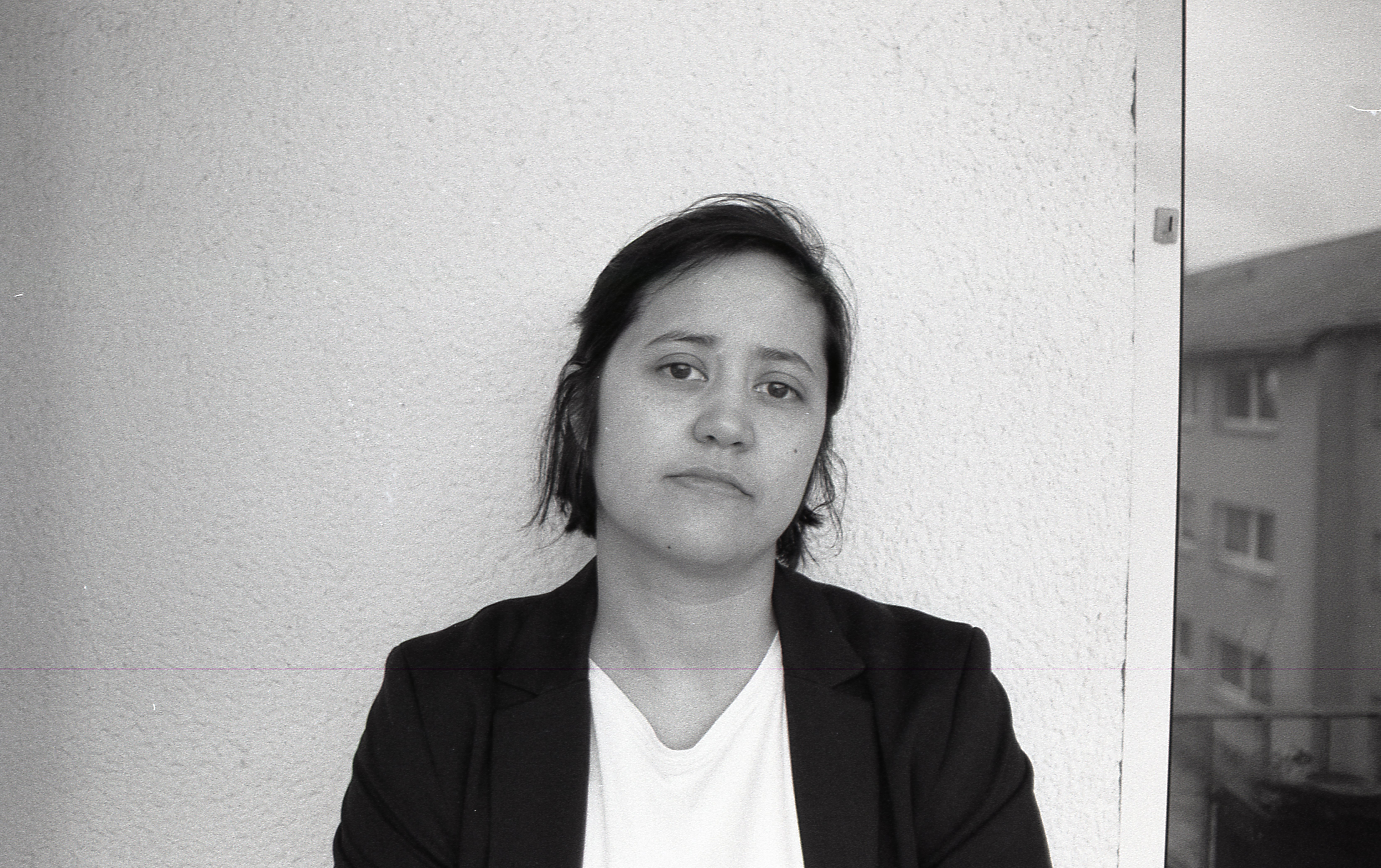 A self portrait of my on my balcony in a white shirt and a black blazer.